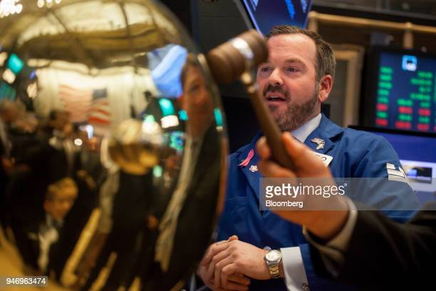 A trader stands next to the ringing of a ceremonial bell celebrating the January 2018 initial public offering of Nine Energy Service Inc on the floor...
