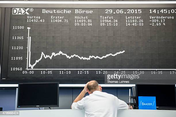 A trader stands under the day's performance graph showing a sharp drop of the German DAX stock market index early today and a partial recovery later...