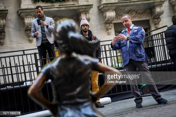 A trader takes a photograph of the 'Fearless Girl' statue after a ceremony to unveil the statue's new location outside the New York Stock Exchange...