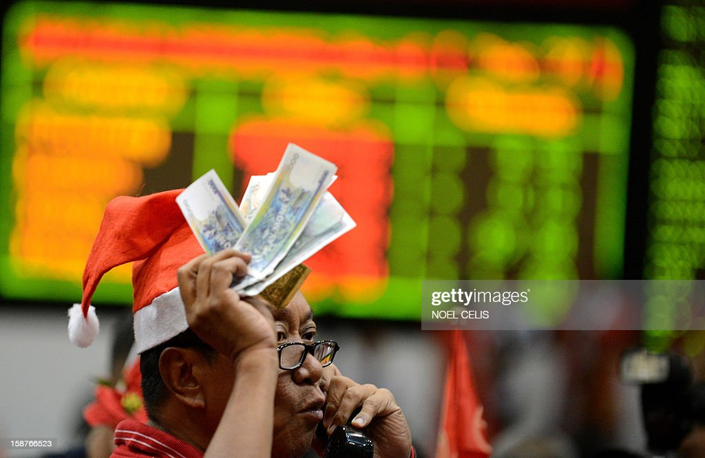 A trader talks on a phone during the closing ceremony of the 2012 trading year at the Philippines Stock Exchange in Manila on December 28, 2012. Asian shares rose on December 28 on hopes of a last-minute deal to avert the US fiscal cliff, despite warnings from a leading Democrat that an agreement is unlikely just days before a year-end deadline.