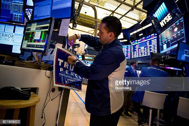 A trader tapes a campaign sign for US Presidentelect Donald Trump and US Vice Presidentelect Mike Pence to a desk on the floor of the New York Stock...