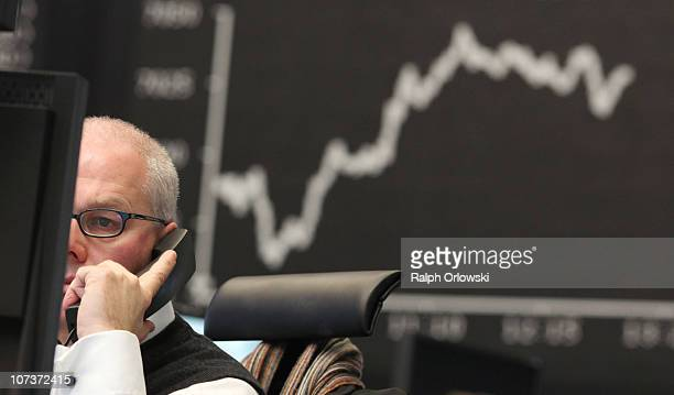 A trader uses a phone during a trading session on the floor of Frankfurt stock exchange on December 7 2010 in Frankfurt am Main Germany The DAX rose...