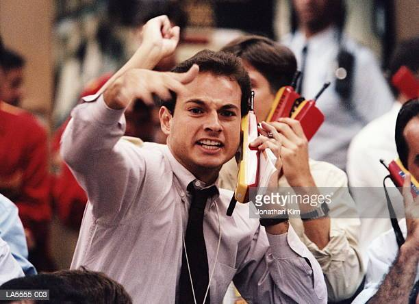 trader using mobile phone, shouting and gesticulating on trading floor - börsensaal stock-fotos und bilder