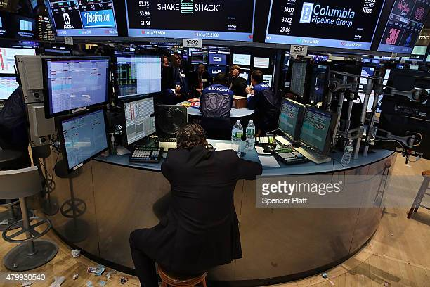 A trader waits on a nearly empty trading floor at the New York Stock Exchange after trading was halted due to a 'technical glitch' on July 8 2015 in...