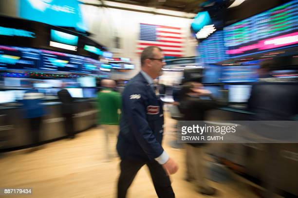 A trader walks across the floor at the closing bell of the Dow Industrial Average at the New York Stock Exchange on December 6 2017 in New York / AFP...