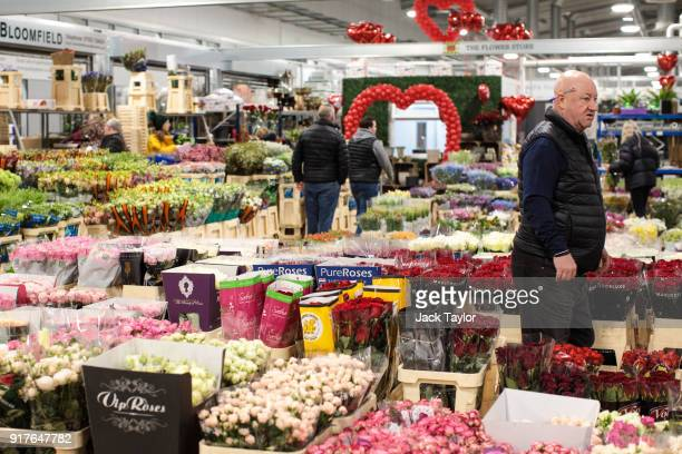 A trader walks among bunches of flowers on display at New Covent Garden Flower Market ahead of Valentine's Day on February 13 2018 in London England...