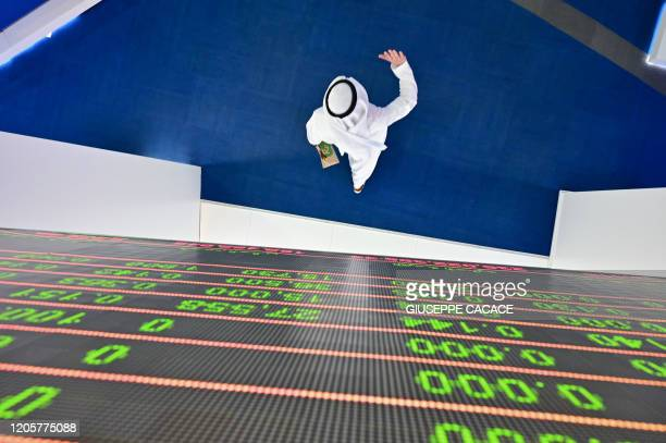 TOPSHOT A trader walks by beneath a stock display board at the Dubai Stock Exchange in the United Arab Emirates on March 8 2020 Saudi's stock...
