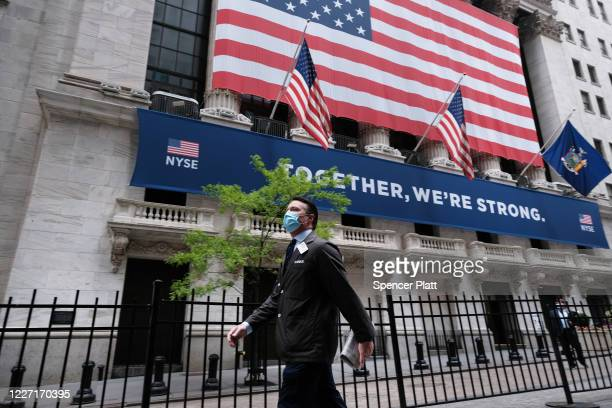 Trader walks by the New York Stock Exchange on the first day that traders are allowed back onto the historic floor of the exchange on May 26, 2020 in...