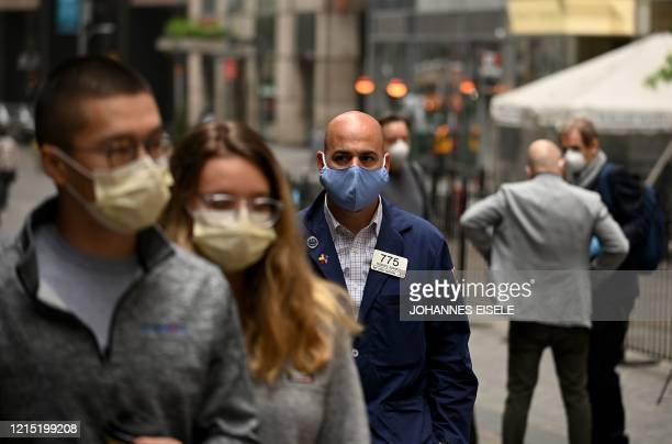 Trader walks in front of the New York Stock Exchange on May 26, 2020 at Wall Street in New York City. - Wall Street stocks surged early May 26, 2020...
