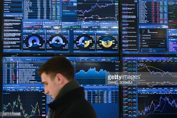 Trader walks past a display showing financial data at the offices of CMC Markets in the City of London on December 10, 2018 after Britain's Prime...