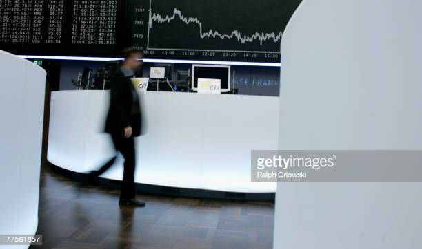 A trader walks past the German DAX Index board on the trading floor of Frankfurt stock exchange on October 30 2007 in Frankfurt Germany German DAX...