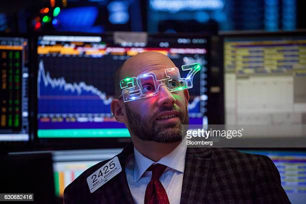 A trader wearing 2017 glasses works on the floor of the New York Stock Exchange in New York US on Friday Dec 30 2016 US stocks pared the biggest...