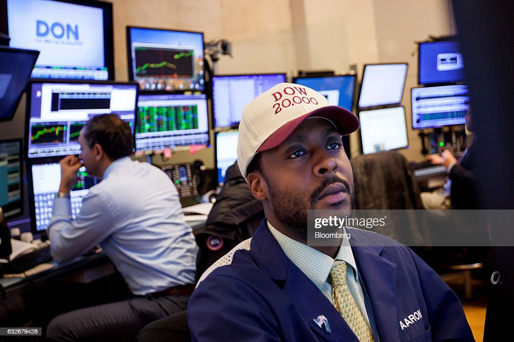 A trader wearing a 'DOW 20,000' hat works on the floor of the New York Stock Exchange (NYSE) in New York, U.S., on Wednesday, Jan. 25, 2017. The Dow Jones Industrial Average climbed past 20,000 for the first time as stocks around the world extended a rally after corporate earnings reignited investors' optimism in economic growth. Bonds sold off with oil. Photographer: Michael Nagle/Bloomberg via Getty Images