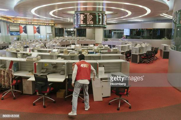Trader wearing a red trading jacket cleans up a booth on the trading floor of the Hong Kong Stock Exchange, operated by Hong Kong Exchanges &...