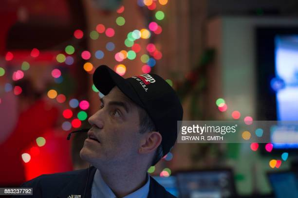 A trader wearing a Trump hat works on the floor at the closing bell of the Dow Industrial Average at the New York Stock Exchange on November 30 2017...