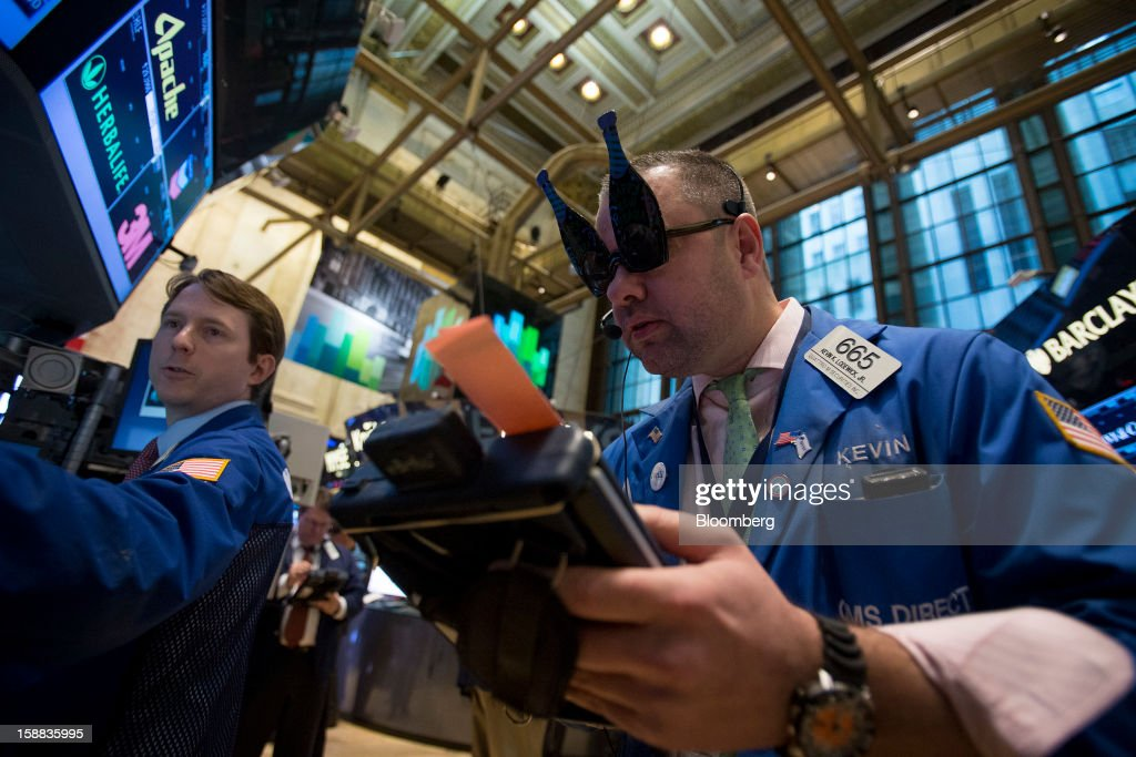 A trader wearing novelty glasses in the shape of champagne bottles works at the New York Stock Exchange (NYSE) in New York, U.S., on Monday, Dec. 31, 2012. Most U.S. stocks gained, rebounding from a five-day slump, as investors weighed prospects for a compromise in federal budget talks. Photographer: Scott Eells/Bloomberg via Getty Images