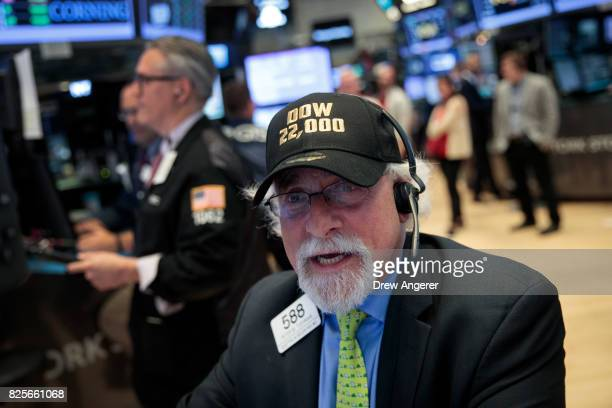 A trader wears a 'Dow 22000' themed hat while working on the floor of the New York Stock Exchange ahead of the closing bell August 2 2017 in New York...