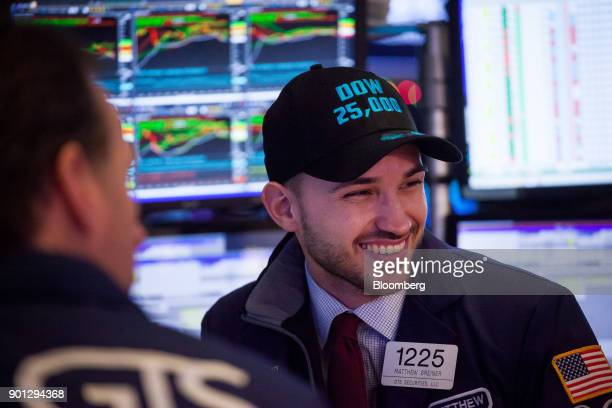 A trader wears a 'Dow 25000' hat while working works on the floor of the New York Stock Exchange in New York US on Thursday Jan 4 2018 It's a new...