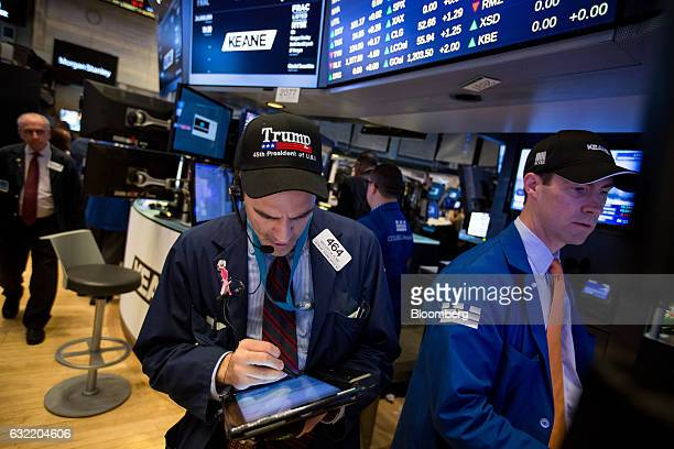 A trader wears a hat displaying the name of US President Donald Trump while working on the floor of the New York Stock Exchange in New York US on...