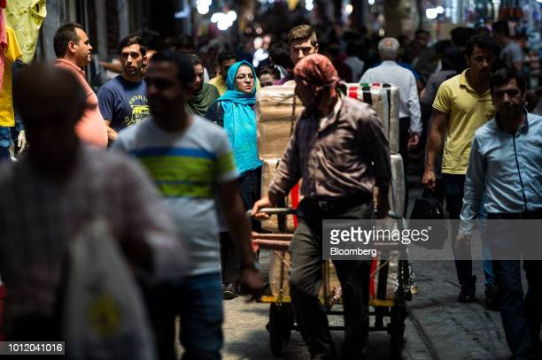A trader wheels a trolley of goods through a retail arcade inside the Grand Bazaar in Tehran Iran on Monday Aug 6 2018 Irans central bank acting on...