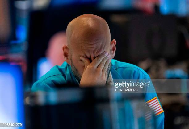 A trader wipes his eyes as he watches stock prices at the New York Stock Exchange August 23 2019 in New York Wall Street stocks tanked Friday after...