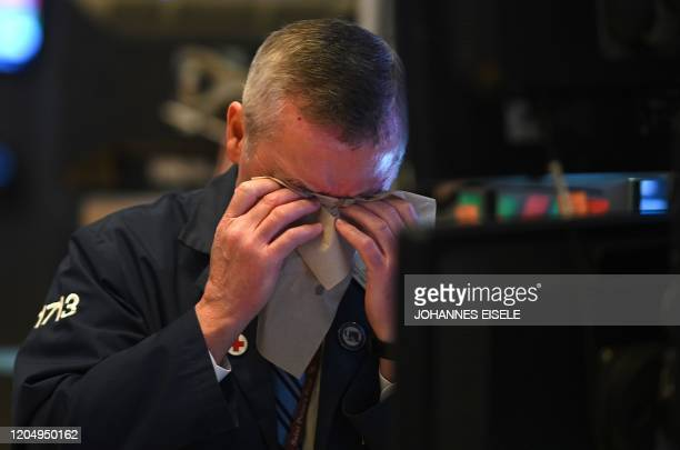 A trader wipes his face as he works during the closing bell at the New York Stock Exchange on March 3 2020 on Wall Street in New York City Stock...