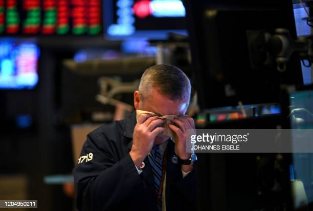 Trader wipes his face as he works during the closing bell at the New York Stock Exchange on March 3, 2020 on Wall Street in New York City. - Stock...