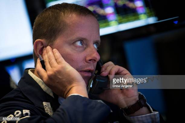 Trader works at his desk on the floor of the New York Stock Exchange ahead of the opening bell, August 11, 2017 in New York City. After a week of...