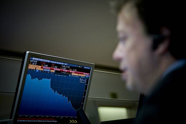 a trader works behind a computer screen in lisbon on april 23 2014