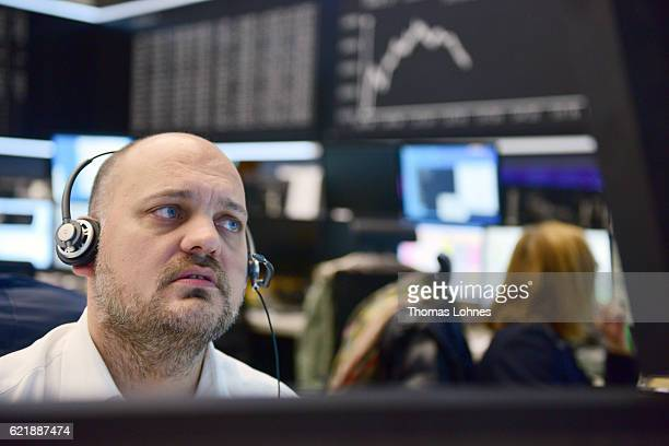 Trader works below the graph showing the day's course of the DAX index at the Frankfurt Stock Exchange on November 9, 2016 in Frankfurt, Germany....