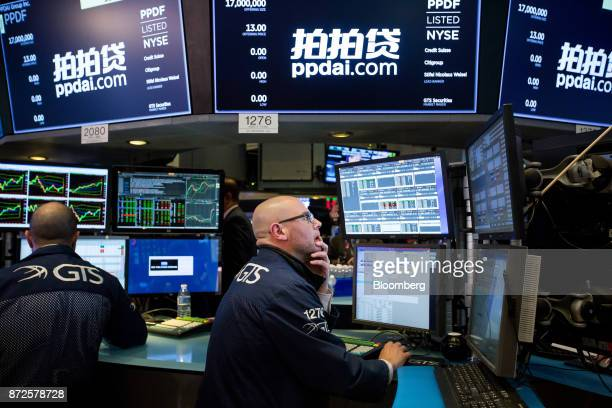 A trader works beneath monitors displaying PPDAI Group Inc signage on the floor of the New York Stock Exchange in New York US on Friday Nov 10 2017...