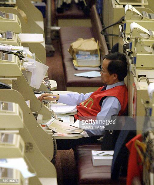 A trader works during afternoon session at the Hong Kong Stock Exchange 05 January 2005 Hong Kong share prices closed sharply lower Wednesday...