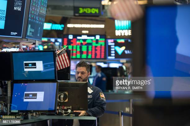 A trader works on the floor at the closing bell of the Dow Industrial Average at the New York Stock Exchange on December 6 2017 in New York / AFP...