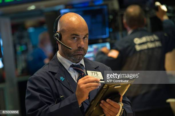 A trader works on the floor at the closing bell of the Dow Jones Industrial Average at the New York Stock Exchange on August 1 2017 in New York Wall...