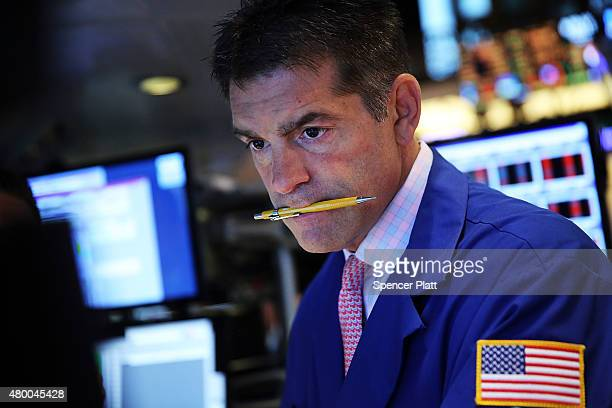 A trader works on the floor of the New York Stock Exchange a day after the market closed for over three hours yesterday due to a 'technical glitch'...