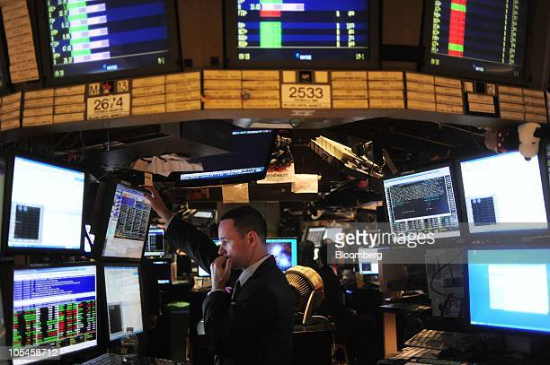A trader works on the floor of the New York Stock Exchange after the opening bell in New York US on Thursday Oct 14 2010 US stocks fell dragging...