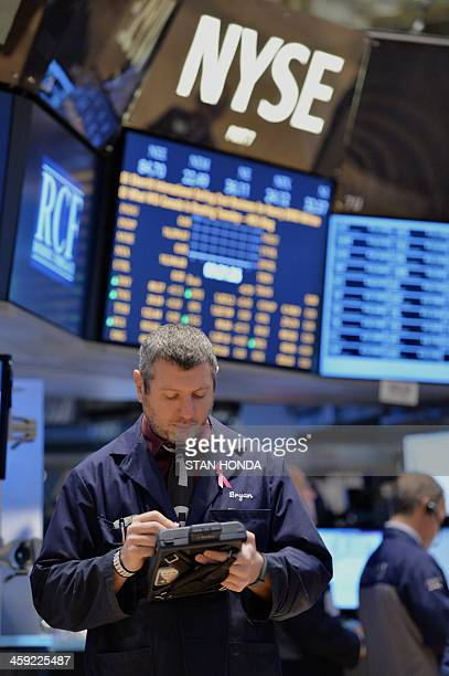 A trader works on the floor of the New York Stock Exchange December 24 2013 in New York US stocks moved higher in a holidayshortened session Tuesday...