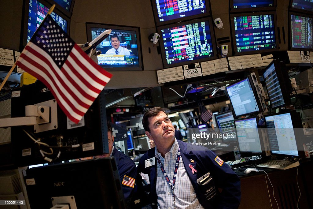 A trader works on the floor of the New York Stock Exchange during morning trading on July 29, 2011 in New York City. The Dow continued a week-long decline during morning trading as the debt crisis debate continues.