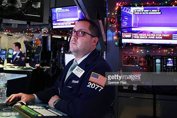 A trader works on the floor of the New York Stock Exchange following an announcement that the Federal Reserve will raise interest rates for the first...