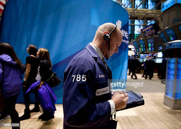 A trader works on the floor of the New York Stock Exchange in New York US on Monday Dec 12 2011 US stocks fell after a twoweek gain in the Standard...