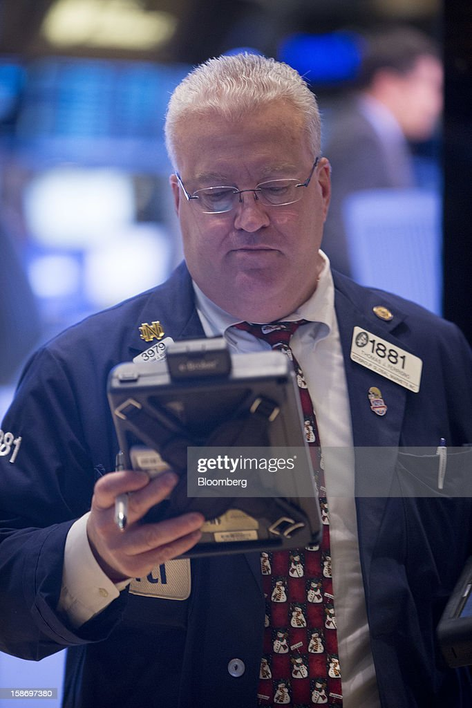 A trader works on the floor of the New York Stock Exchange (NYSE) in New York, U.S., on Monday, Dec. 24, 2012. Americans have missed out on almost $200 billion of stock gains as they drained money from the market in the past four years, haunted by the financial crisis. Photographer: Scott Eells/Bloomberg via Getty Images
