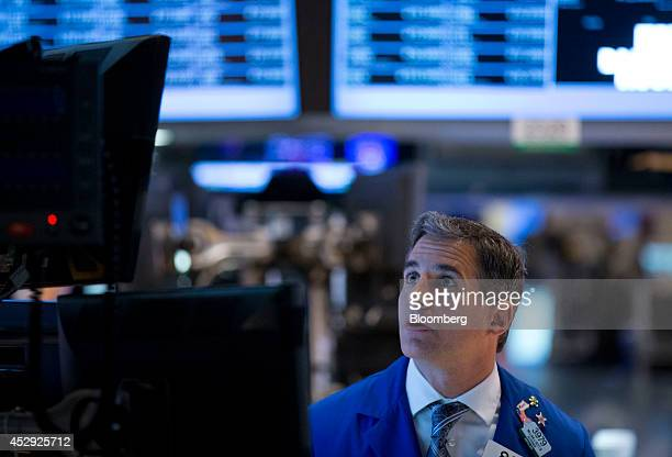 A trader works on the floor of the New York Stock Exchange in New York US on Wednesday July 30 2014 US stocks erased gains as declines in industrial...