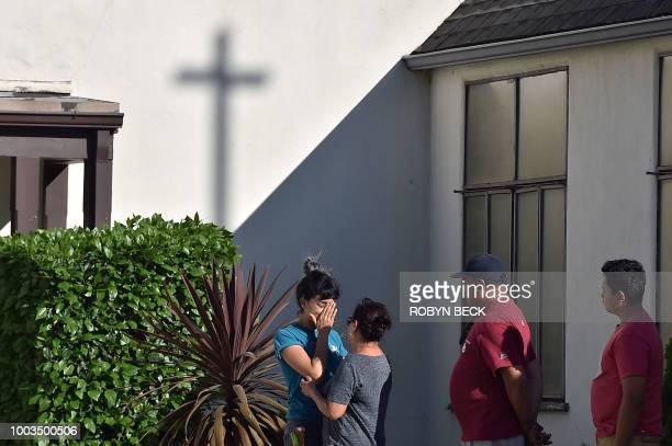 A TraderJoe's employee is comforted after a suspect barricaded inside the supermarket in Silverlake Los Angeles on July 21 2018 A suspect wanted in...