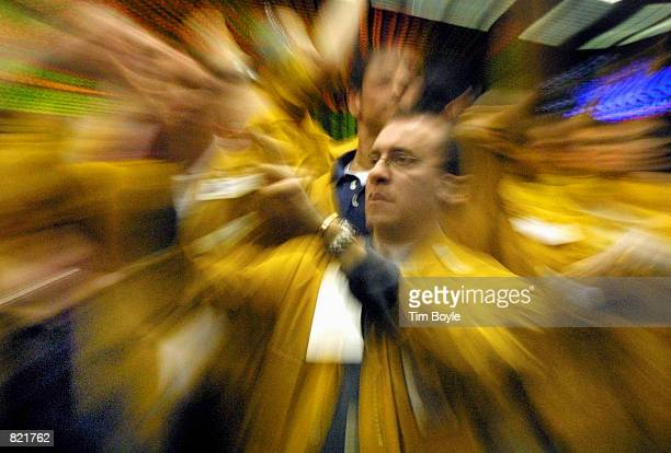 Traders and clerks flash handsignals as they work in the Eurodollar Futures pit March 20 2001 at the Chicago Mercantile Exchange after the Federal...