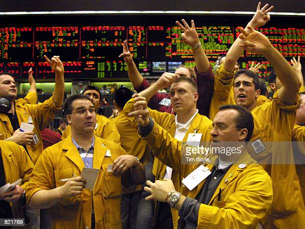 Traders and clerks flash handsignals as they work the Eurodollar Futures pit March 20 2001 at the Chicago Mercantile Exchange after the Federal...