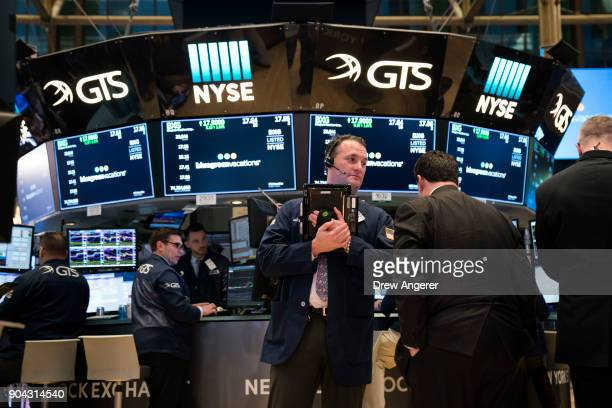 Traders and financial professional work ahead of the closing bell on the floor of the New York Stock Exchange January 12 2018 in New York City The...