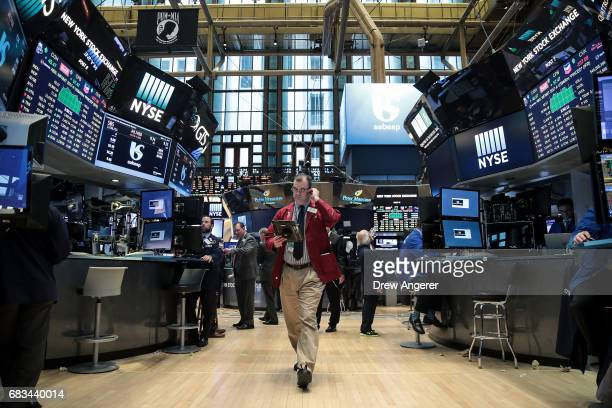 Traders and financial professional work on the floor of the New York Stock Exchange ahead of the closing bell May 15 2017 in New York City The Dow...