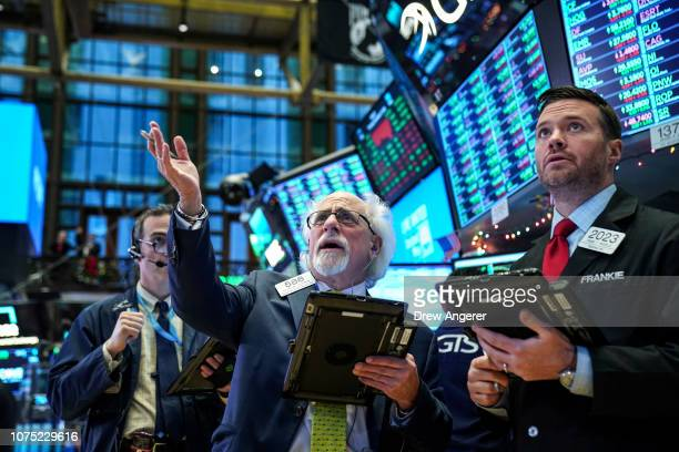 Traders and financial professionals work ahead of the closing bell on the floor of the New York Stock Exchange December 27 2018 in New York City...