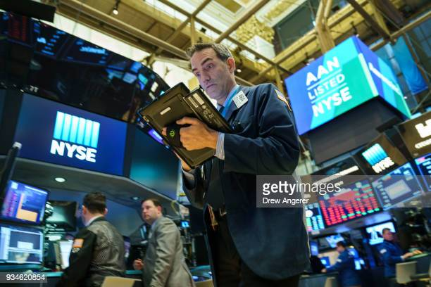 Traders and financial professionals work ahead of the closing bell on the floor of the New York Stock Exchange March 19 2018 in New York City The Dow...