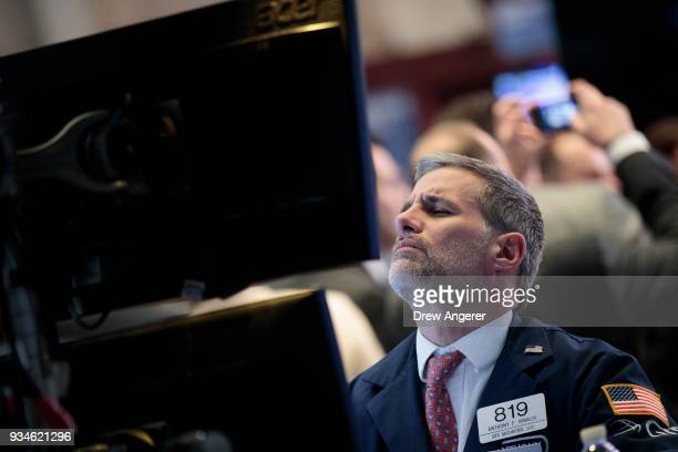 Traders and financial professionals work ahead of the closing bell on the floor of the New York Stock Exchange , March 19, 2018 in New York City. The...